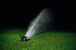 Leinwanddruck Bild - automatic lawn sprinkler spraying water over golf course green grass at night