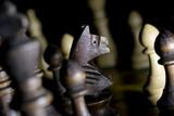Koń skoczek i Szachy na szachownicy czarne tło makro