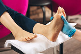 Leg massage. Close up of female hands touching foot while woman working at nail bar