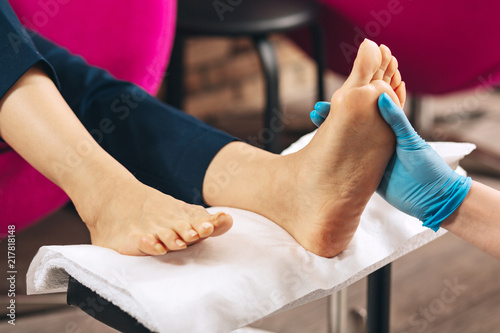 Canvas Pedicure Leg massage. Close up of female hands touching foot while woman working at nail bar