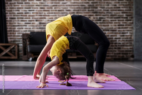 Plakat Woman and child girl practicing yoga together at home, standing in bridge pose
