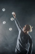 Quadro Blond juggler with white balls on black background