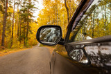 Black car on the road in the forest in autumn