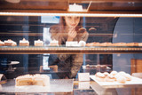 Smiling woman at camera through the showcase with sweet and cakes in modern cafe interior - 217824195