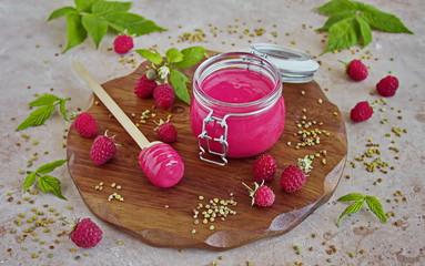 Homemade berry whipped honey with fresh raspberries in a glass jar, fresh raspberries on a wooden tray © Lena