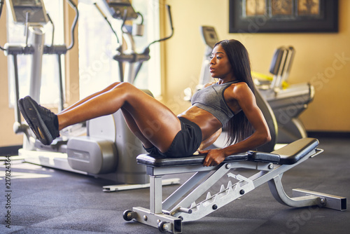 Wall mural fit african american woman working out and stretching in gym