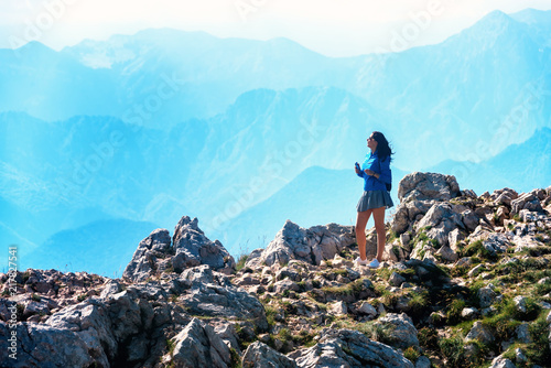 Foto Murales Young woman stands on the rocks and looks at the mountain.