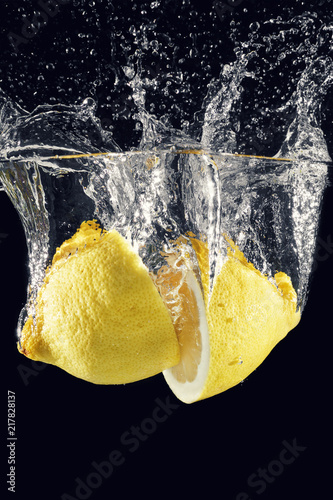 Foto Murales bursts and splashes from a lemon thrown into the water. Black background.