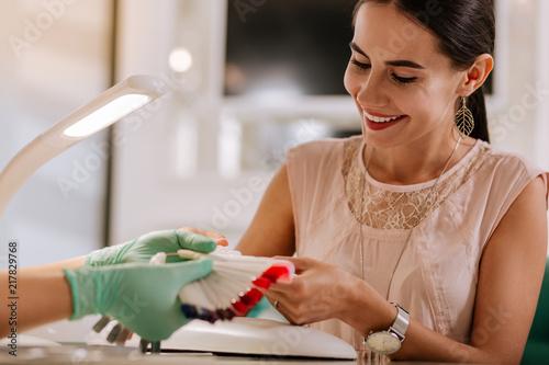 Wybór koloru. Ciemnowłosa kobieta czuje się naprawdę ciekawa podczas wybierania koloru dla swojego przyszłego manicure