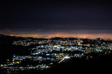 City at night over the hill
