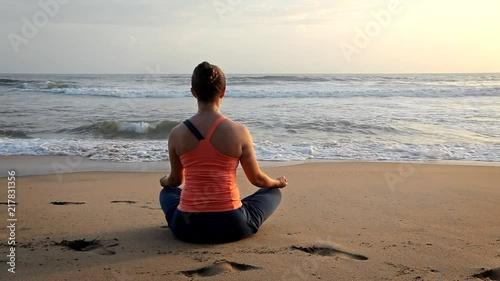 Wall mural Woman doing yoga oudoors at beach - Padmasana lotus pose