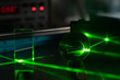 Green laser on optical table in a quantum optics lab.