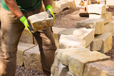 Landschaftsgärtner beim Bau einer Trockenmauer aus Sandstein