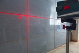 Installation of new tiles on the wall using a laser level - 217842510