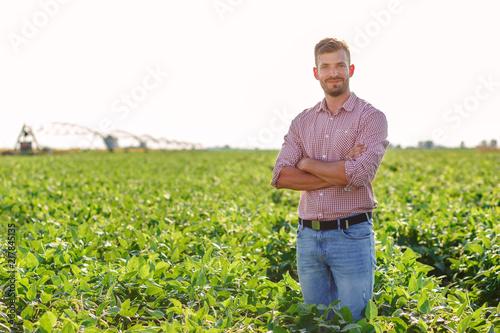 Portrait of young farmer standing in soybean field.
