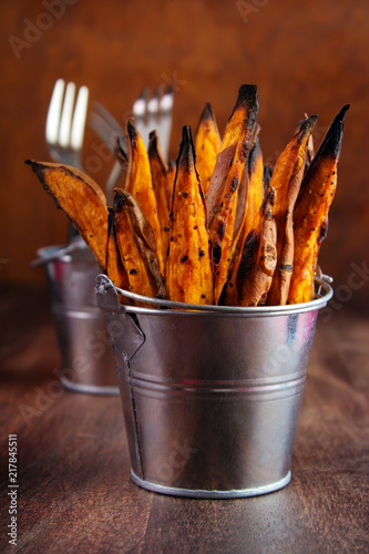 Foto Murales Homemade baked sweet potato fries with skin in  metal serving bucket on wooden background