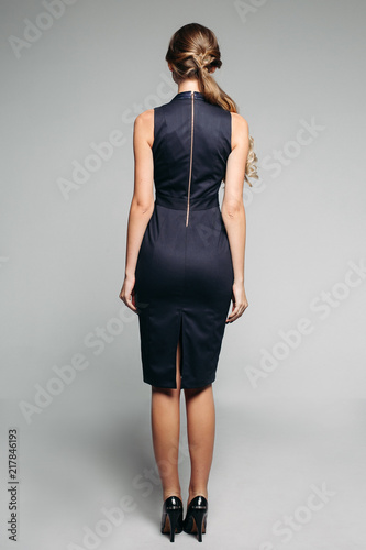 Back View Of Incognito Blonde Woman With Long Hair In Tail Wearing Elegant Office Dress And
