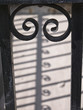 Silhouette of antique cast iron railing with beautiful shadow on the ground. Selective focus, blurred background.