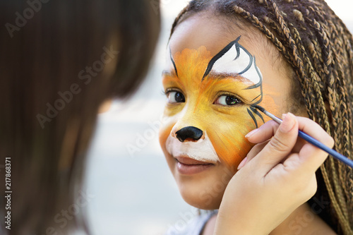 Foto Murales Little girl getting her face painted by face painting artist.