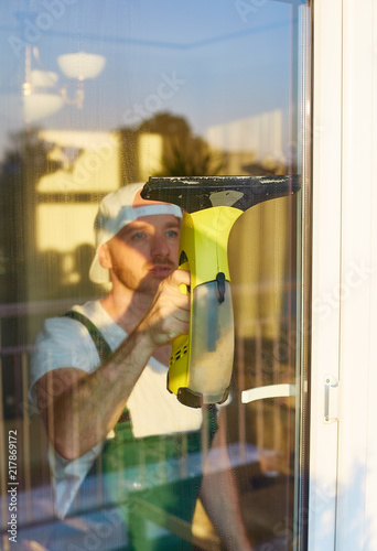 Foto Murales A man from a cleaning company washing window with professional equipment.