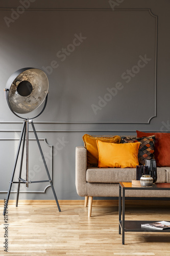 Couch with colorful pillows standing in real photo of grey living room interior with studio lamp, molding on wall and metal table with decor
