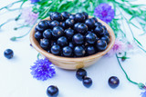 Fresh berries of black currant in a plate on a table. For a diet and saturation with vitamins