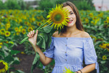 Young beautiful girl in dress and hat in field with sunflowers