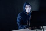 Anonymous and masked hacker under hoodie using computer isolated over dark background - illegal online internet criminal concept. - 217887753