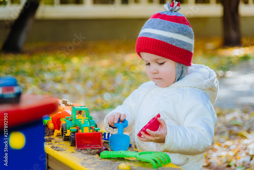 little kid plays in the sandbox with toys