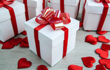 white gift box on the background of other gift boxes with shapes of hearts