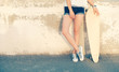 Girl standing near wall with her legs crossed holding her longboard leaning back weared wall, a lot of copyspace