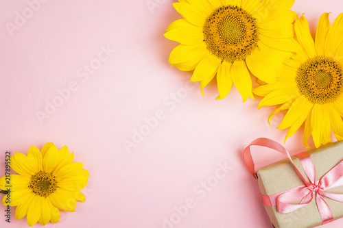 Foto Murales Pink background with yellow sunflowers and gift box.