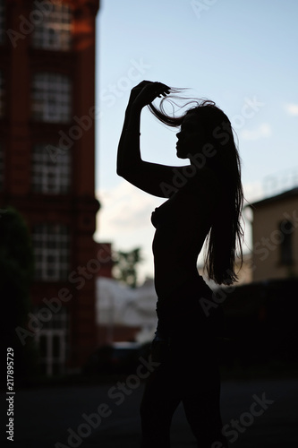 Silhouette of half nakd woman in the city. Fashion art photo.