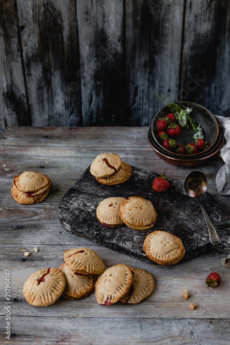 high angle view of tasty cookies with strawberries on wooden table