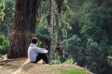 Hombre sentado en la cima de una montaña contemplando el bosque que lo rodea en calma