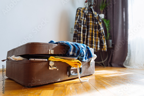 Foto Murales overloaded suitcase with clothes. travel concept. bag with garment