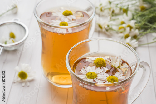 Fototapeta Cup of tea and chamomile flowers on wooden background