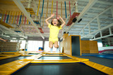 beautiful little girl jumping on a trampoline indoors