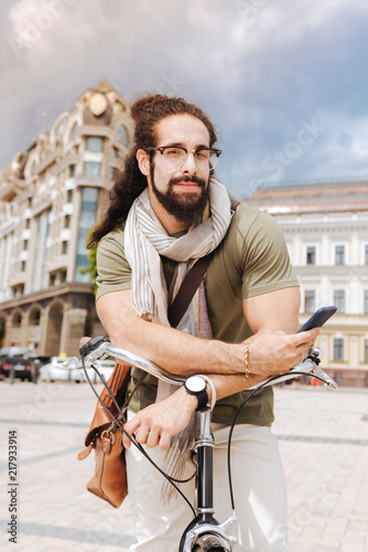 Foto Murales In the city. Joyful nice man looking at you while standing with his bicycle