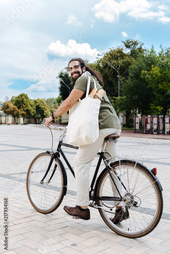 Poster Ecological vehicle. Pleasant happy man smiling while riding bike in the city