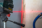Installation of new tiles on the wall using a laser level - 217935501