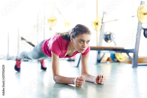 Poster Young fit woman training in gym and doing plank exercise looking forward with determination