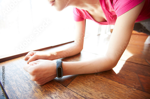 Plexiglas Fitness Unrecognizable woman with smartwatch performing plank exercise on wooden floor in gym