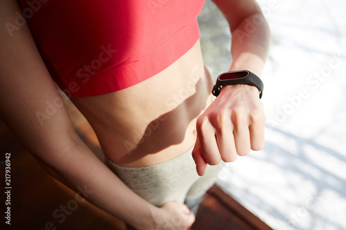 Sticker Crop woman in sportswear checking pulse on fitness tracker while standing near window in gym