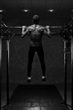 Back view of muscular man with naked torso doing pull up exercise on horizontal bar. Gymnastics, fitness workout in gym. - 217939108