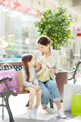 Playful woman with little girl sitting on bench in shopping center with paper bags and playing with toy in daylight