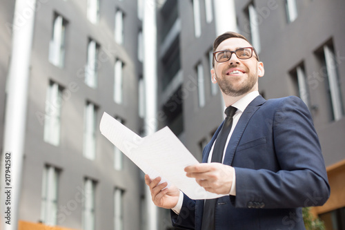 From below shot of happy bearded man in suit and glasses holding papers and looking away on background of office building