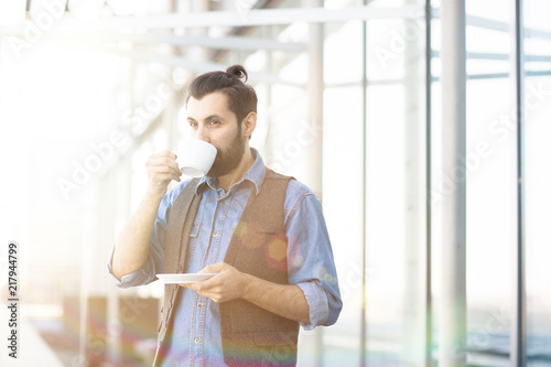 Wall mural Trendy adult man with beard having cup of coffee and drinking in relaxation looking pensively away in bright light