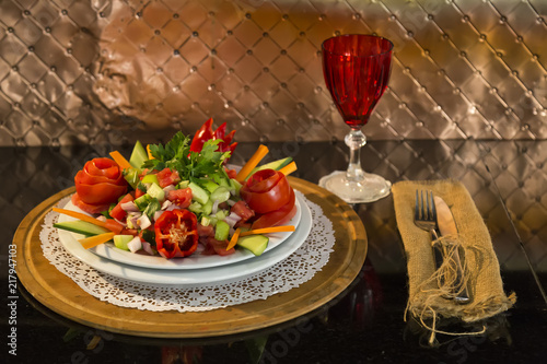 a plate of Turkish Coban salad,glass,fork,knife and wicker service napkins on the black background for restaurant and cafe concept. - 217947103