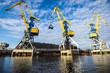Leinwanddruck Bild - A view of the port cranes against blue sky. Riga, Latvia